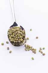 Green mung bean in spoon isolated on white background