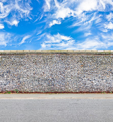 stone wall with road and skies horizontal seamless image