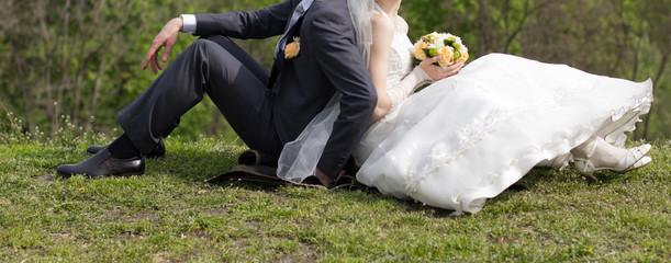 Bride and groom sitting in a meadow