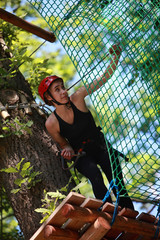 Young caucasian attractive woman climbing in adventure rope park