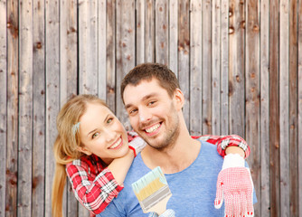 smiling couple covered with paint with paint brush