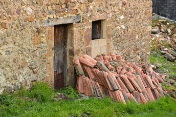 tejas apiladas junto a una casa antigua de piedra