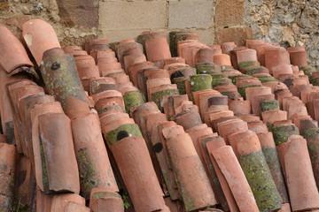 conjunto de tejas apiladas contra un muro de piedra
