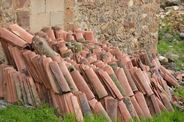 tejas apiladas en un muro de piedra