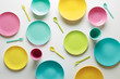 Colorful plastic dishes on white background