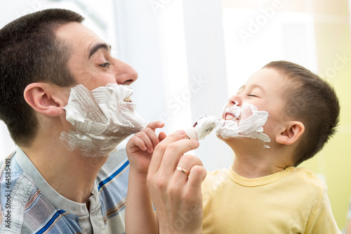 playful father and his son shaving and having fun in bathroom