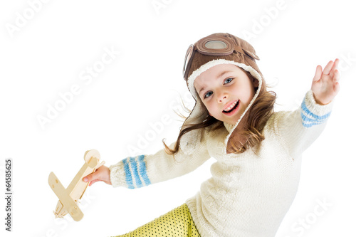 funny kid dressed as pilot and playing with wooden airplane toy