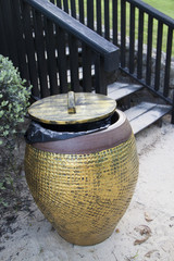 Jar-shaped bin with lid at the stairs