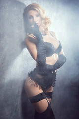 Young and beautiful cabaret dancer in sexy vintage lingerie smok