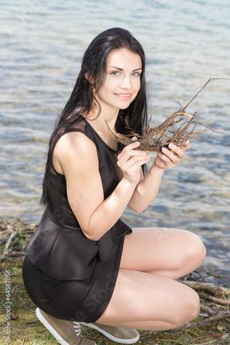 canvas print picture Junge Frau am Wasser mit Treibholz und schoenen Beinen