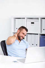 Young businessman has pain of the cervical at work