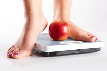 A pair of female feet standing on a bathroom scale with red appl