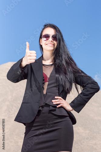canvas print picture Maedchen mit Taille und Daumen nach oben vor Sand