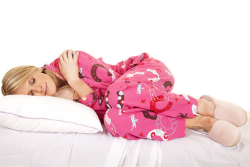 Woman pink pajamas lay side sleep knees up