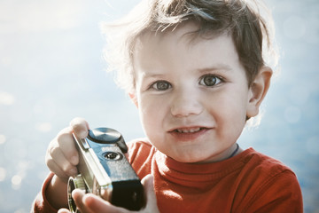 Portrait of a smiling cute boy with retro camera in sunshine