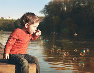 Little boy blowing soap bubbles at a lake