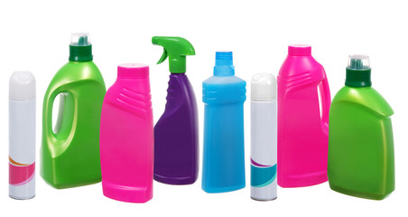 Many different plastic bottles of cleaning products on white
