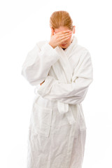 Young woman standing in bathrobe covering her face with her hand