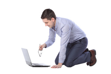 man kneeling in front of a laptop isolated on white