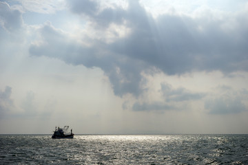 Silhouette of a fishing boat offshore