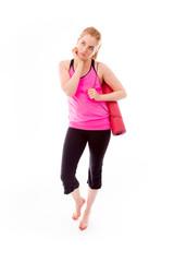 Young woman carrying exercising mat looking sad