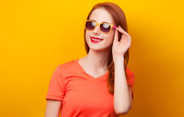 Happy redhead girl in sunglasses on yellow background
