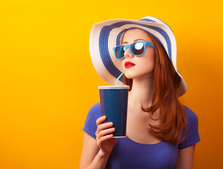 Redhead girl with drink and sunglasses on yellow background