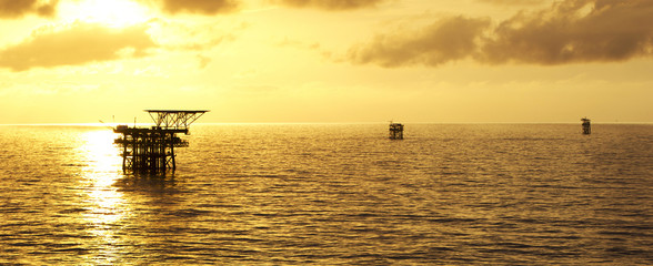 Silhouette of offshore oil rigs at sunrise