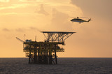 A helicopter transports roughnecks to a rig