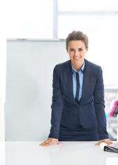Portrait of smiling business woman near flipchart