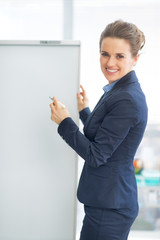 Happy business woman writing in flipchart