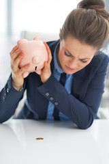 Closeup on business woman shaking out coin from piggy bank