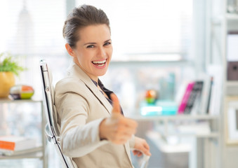 Happy business woman showing thumbs up