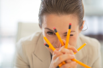 Portrait of business woman holding pencils