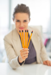 Closeup on business woman showing pencils