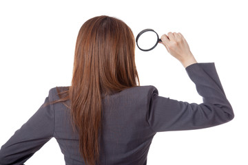 Back view of Asian businesswoman use magnifying glass