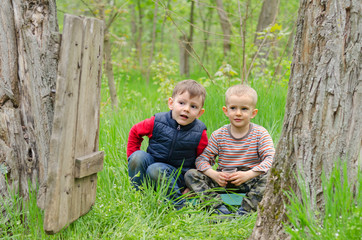 Two cute young boys playing in woodland