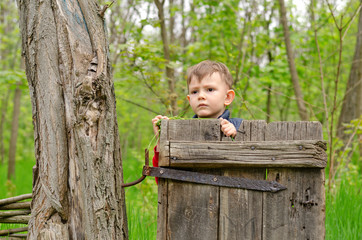 Cute little boy peering over an old wooden gate
