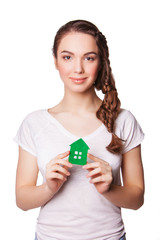 young smiling woman holding green house. isolated on white