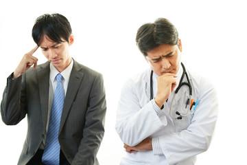 心配そうな表情の医師と患者