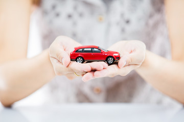 Woman hand with holding red car