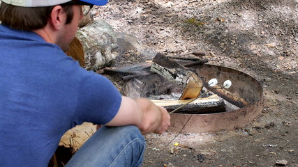 Man with Hat Roasting Marshmallows on a Campfire (Medium)