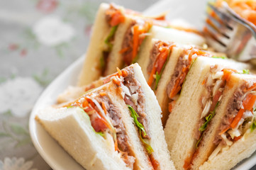 Small pieces Tuna Salad Sandwiches on table .
