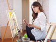 Woman paints with oil colors on easel