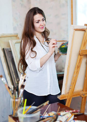 Long-haired girl paints on easel