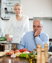 Mature couple having quarrel at kitchen