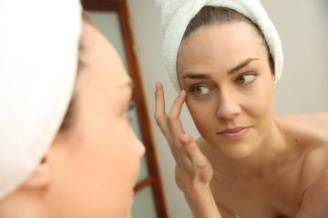 Woman in bathroom looking in mirror