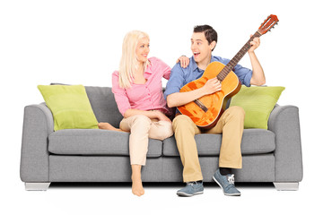 Man playing on guitar with his girlfriend
