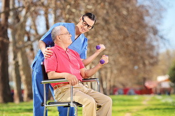 Male nurse and a senior lifting dumbbells in park