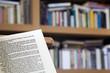 Página abierta en escorzo con biblioteca al fondo